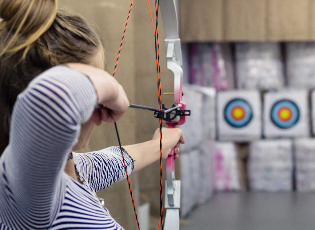 Image of girl shooting bow and arrow at archery tournament